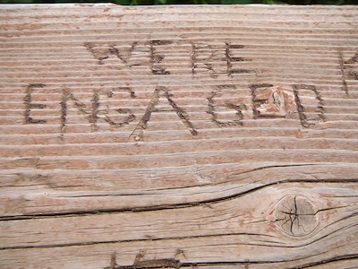 "A wood plate with ""we're engaged"" curved in it"