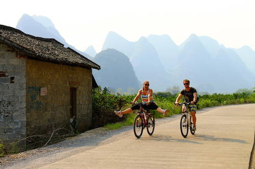 Jill and Josh enjoying passive income by riding bicycles in exotic locations
