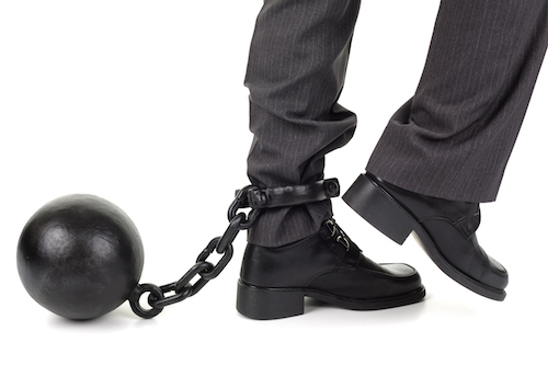 ball and chain holding leg of businessman